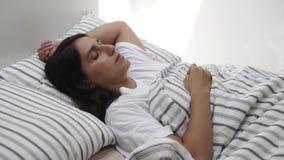La giovane donna si trova a letto con gli occhi chiusi, signora sta dormendo stock footage