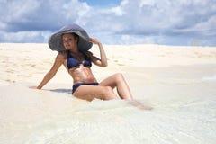 La giovane donna si trova sulla spiaggia Immagine Stock Libera da Diritti