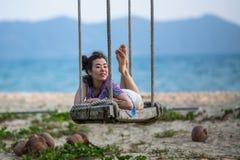La giovane donna si trova sulle oscillazioni sulla spiaggia del mare immagini stock