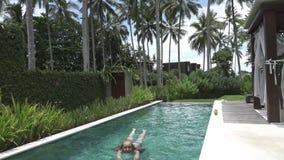 La giovane donna snella con capelli lunghi in Bikin nuota nello stagno sotto le palme nella località di soggiorno tropicale stock footage