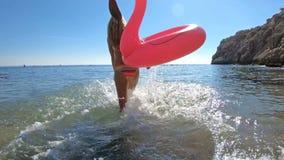 La giovane donna snella gode del mare e del sole che cammina nell'acqua con un fenicottero gonfiabile rosa video d archivio
