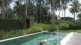La giovane donna snella ha un resto nello stagno nella località di soggiorno tropicale sotto le palme stock footage