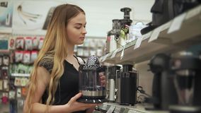 La giovane donna sola sta confrontando il modello delle macchine del caffè in un negozio dell'hardware archivi video