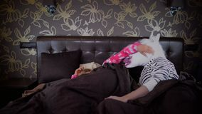 La giovane donna sonnolenta in pigiama sveglia l'uomo insolito video d archivio