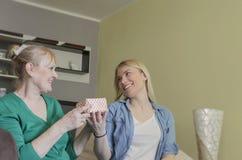 La giovane donna sorprende sua madre con un contenitore di regalo immagine stock libera da diritti