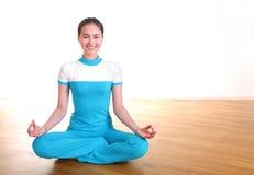 La giovane donna sorridente che si siede facendo il loto di yoga propone Fotografie Stock