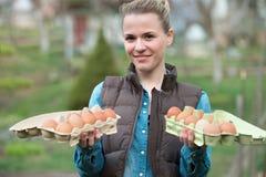 La giovane donna sorridente che tiene il pollo fresco eggs in mani all'aperto immagine stock libera da diritti
