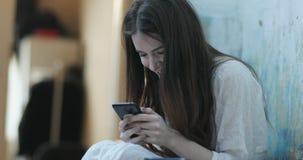 La giovane donna sorridente con capelli scuri lunghi legge qualcosa in suo smartphone che si siede sul pavimento in una stanza video d archivio