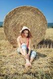 La giovane donna sorridente dell'agricoltore pende il mucchio di fieno durante il raccolto vicino Immagini Stock