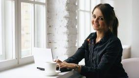 La giovane donna sorridente dello studente si siede in caffetteria alla tavola con il computer portatile all'interno immagine stock libera da diritti