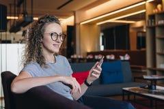 La giovane donna sorridente di affari in vetri si siede sullo strato nell'ingresso dell'hotel, caffè e tiene lo smartphone, mentr Fotografia Stock Libera da Diritti