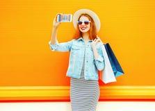 La giovane donna sorridente di modo prende un autoritratto dell'immagine su uno smartphone Fotografia Stock