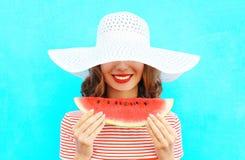 La giovane donna sorridente felice del ritratto di modo sta tenendo una fetta di anguria in un cappello di paglia immagine stock libera da diritti