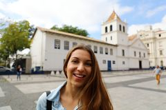 La giovane donna sorridente felice nel centro urbano di Sao Paulo con il patio fa il punto di riferimento sui precedenti, Sao Pau immagini stock
