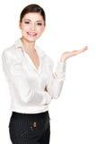 La donna mostra qualcosa sulla palma isolata su bianco Fotografia Stock Libera da Diritti