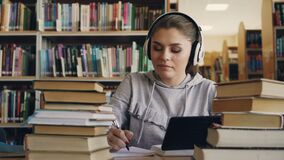 La giovane donna sorridente positiva in cuffie bianche sta sedendosi alla tavola in biblioteca universitaria che tiene la compres archivi video