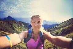 La giovane donna sorridente prende un selfie sul picco di montagna Fotografia Stock