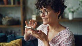 La giovane donna sorridente sta componendo il numero di telefono poi che parla in smartphone della tenuta del modo dell'altoparla video d archivio