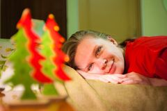 La giovane donna sorridente vede sui giocattoli dell'albero di natale Fotografie Stock Libere da Diritti