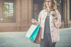 La giovane donna sorridente in vetri porta i sacchetti della spesa e tiene la tazza di caffè La ragazza ha comprato i presente pe Immagini Stock