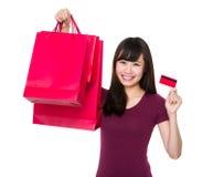 La giovane donna sostiene con il sacchetto della spesa e la carta di credito Immagine Stock
