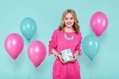 La giovane donna splendida in attrezzatura del partito che giudica un presente isolato sopra il blu pastello ha colorato il fondo Fotografie Stock Libere da Diritti