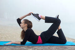 La giovane donna sportiva allunga durante l'allenamento di addestramento all'aperto Fotografia Stock Libera da Diritti