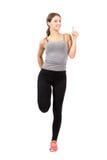 La giovane donna sportiva che allunga la gamba con i pollici aumenta il gesto Fotografia Stock Libera da Diritti
