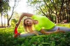 La giovane donna sportiva che fa la forma fisica esercita l'allungamento nel parco Fotografie Stock