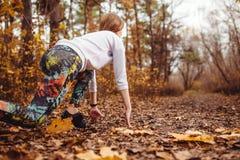 La giovane donna sportiva di Concentrared è pronta a funzionare all'aperto nel parco di autunno Fotografia Stock Libera da Diritti