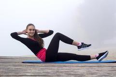 La giovane donna sportiva fa gli esercizi dell'ABS durante l'allenamento di forma fisica fuori Fotografia Stock