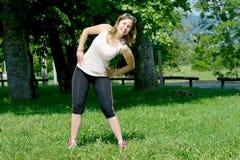 La giovane donna sportiva fa l'allungamento degli esercizi Fotografie Stock Libere da Diritti