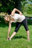 La giovane donna sportiva fa l'allungamento degli esercizi Immagini Stock