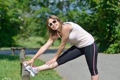 La giovane donna sportiva fa l'allungamento degli esercizi Immagine Stock Libera da Diritti