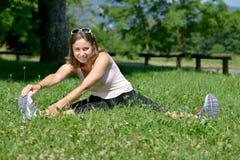 La giovane donna sportiva fa l'allungamento degli esercizi Fotografia Stock