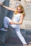 La giovane donna sportiva fa l'allungamento delle gambe Immagini Stock