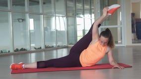 La giovane donna sportiva fa l'esercizio d'allungamento difficile sulla stuoia della palestra mentre si prepara nella palestra Fotografia Stock