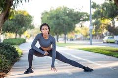 La giovane donna sportiva nell'allenamento copre l'allungamento su un percorso della bici Fotografia Stock