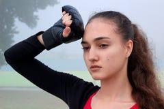 La giovane donna sportiva riposa durante l'allenamento di addestramento di pugilato all'aperto Fotografie Stock