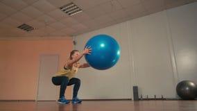 La giovane donna sportiva sta facendo gli edifici occupati con Fitball alle mani nella palestra di addestramento video d archivio
