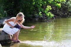 La giovane donna spruzza l'acqua Immagine Stock