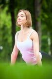 La giovane donna sta allungando nel parco Fotografie Stock Libere da Diritti