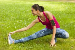 La giovane donna sta allungando nel parco Immagine Stock