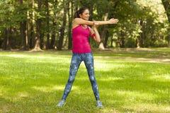 La giovane donna sta allungando nel parco Immagine Stock Libera da Diritti