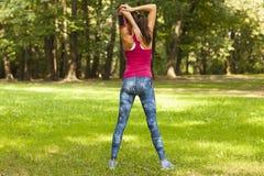 La giovane donna sta allungando nel parco Fotografia Stock