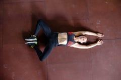 La giovane donna sta allungando sul pavimento dopo la formazione Immagini Stock