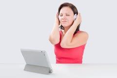 La giovane donna sta ascoltando musica Fotografia Stock