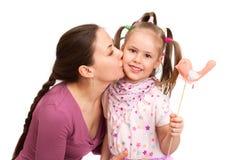 La giovane donna sta baciando la bambina Fotografia Stock