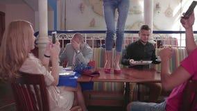 La giovane donna sta ballando sulla tavola in un ristorante stock footage
