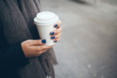 La giovane donna sta bevendo il caffè sulla via mentre camminava il giorno di inverno freddo Immagini Stock Libere da Diritti